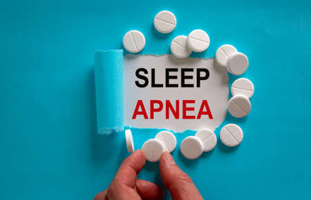 The text 'sleep apnea' appearing behind torn blue paper. White pills and male hand.