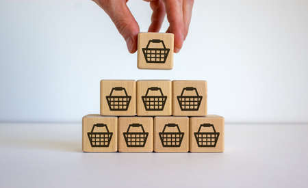 Male hand placing a cube with shopping cart symbol on top of a pyramid. White table. Beautiful white background, copy space. Sale volume increase make business grow. 写真素材