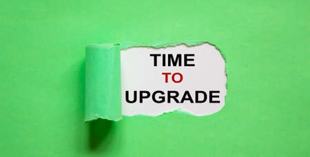 The text 'time to upgrade' appearing behind torn green paper.