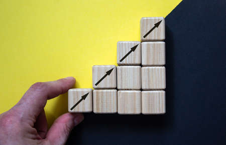 Business concept growth success process, Close up man hand arranging wood block stacking as step stair on paper yellow and black background, copy space.