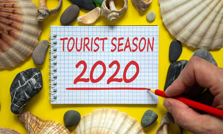 Male hand with red pencil writing 'tourist season 2020' on white note. Beautiful yellow background. Sea stones and seashells. Concept.
