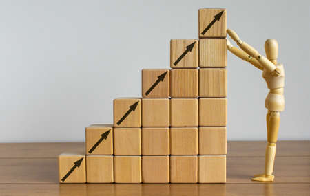 Business concept growth success process. Wooden model of human arranging wood block stacking as step stair on wooden table. Beautiful white background, copy space. Foto de archivo - 150378490