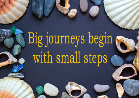 Text 'big journeys begin with small steps' on a beautiful black background. Sea stones and seashells. Concept. Stock fotó