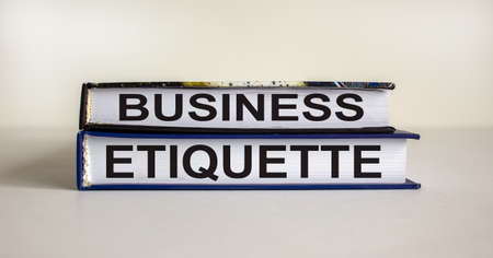 Books with text 'business etiquette' on beautiful white table. White background. Business concept. Copy space.