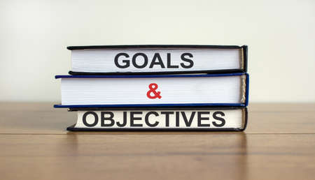 Books with text 'goals and objectives' on beautiful wooden table. White background. Business concept. Copy space.