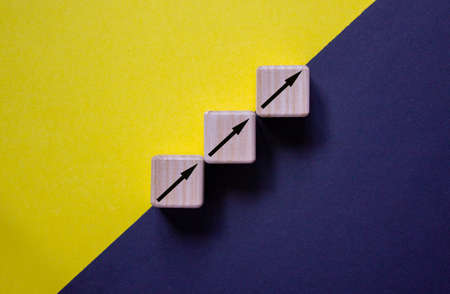 Business concept growth success process. Wood block stacking as step stair on paper yellow and black background, copy space.