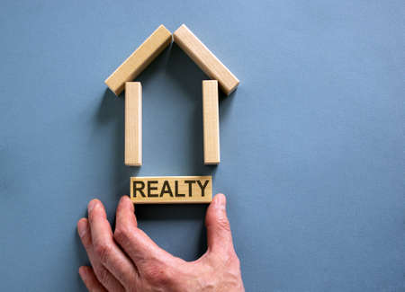 Male hand builds a model of a wooden house from wooden blocks. Word 'realty'. Copy space. Business concept. Beautiful blue background. Banco de Imagens