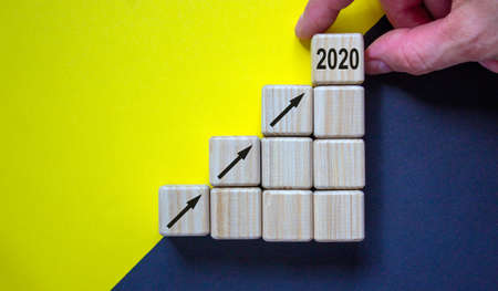 Business concept growth 2020 success process. Close up man hand arranging wood block stacking as step stair on paper yellow and black background, copy space. Foto de archivo - 150380650