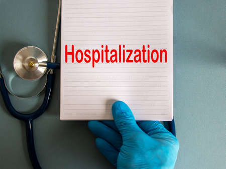 Hand in blue glove, white card with word hospitalization and stethoscope.