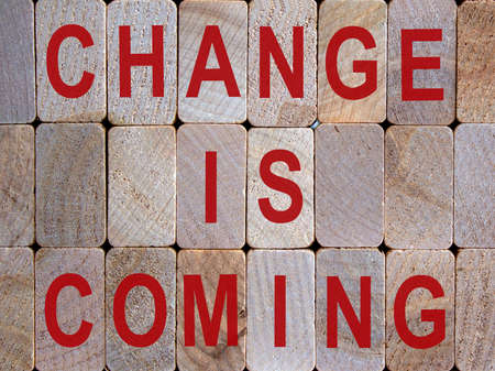 Wooden blocks form the words 'change is coming'. Beautiful wooden background.