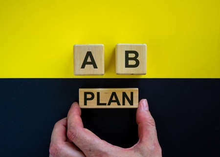 Businessman holds a block with word 'plan'. Wooden cubes with letters A and B. Beautiful yellow and black background. Copy space. Concept of choice. Archivio Fotografico