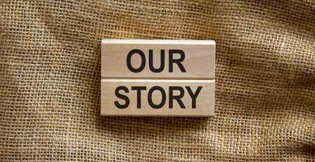 Wooden blocks form the text 'our story' on beautiful canvas background. Business concept.