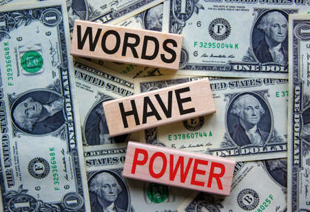 Concept text 'words have power' on wooden blocks on a beautiful background from dollar bills. Business concept.