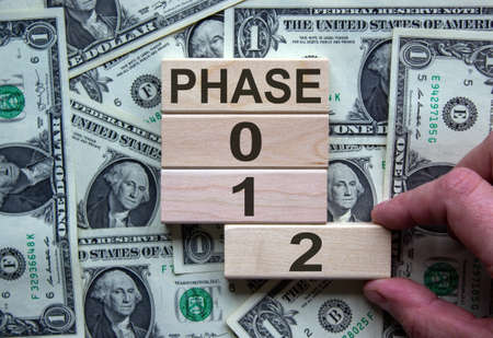 Wooden blocks form the words 'phase, 0, 1, 2' on background from dollar bill. Male hand. Beautiful background. Business concept.