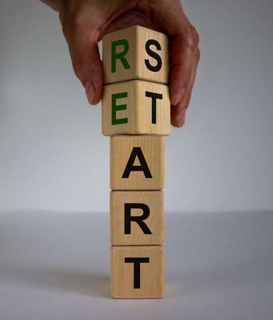 Concept word 'restart' on cubes on a beautiful wooden table. Male hand. White background. Business concept. Copy space.