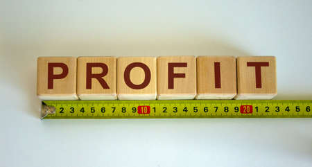 'Profit' word on cubes arranged behind the ruler on beautiful white background. Concept. Banco de Imagens