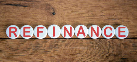 The words 'refinance' on white circles on wooden table. Beautiful background, copy space.