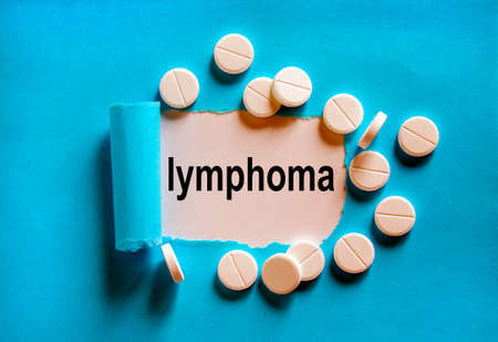 The word 'lymphoma' appearing behind torn blue paper. White pills. Beautiful blue and white background.