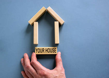 Male hand builds a model of a wooden house from wooden blocks. Words 'your house'. Copy space. Business concept. Beautiful blue background.