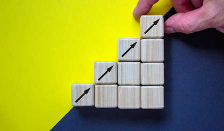 Business concept growth success process. Close up man hand arranging wood block stacking as step stair on paper yellow and black background, copy space.