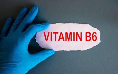Hand in blue glove with white small paper. Concept word vitamin b6.