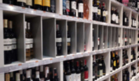 Alcohol showcase blurred background. Blurred abstract background of shelf in supermarket