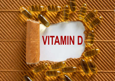 The text 'vitamin d' appearing behind torn brown paper. Yellow pills.
