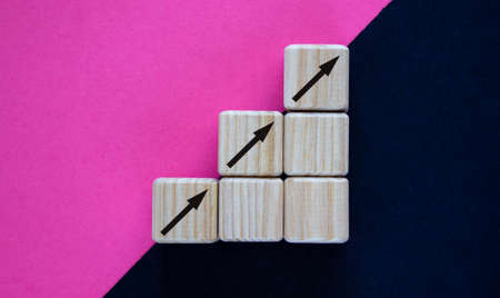 Business concept growth success process. Wood block stacking as step stair on paper purple and black background, copy space.