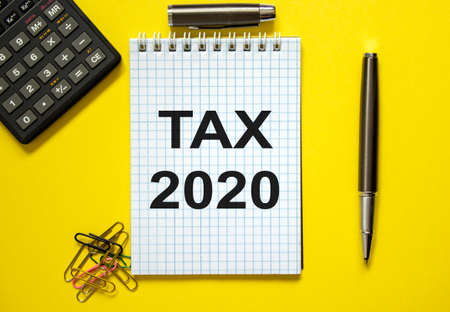 White note with inscription 'tax 2020' on beautiful yellow background, colored paper clips, metalic pen, cap and calculator. Business concept.