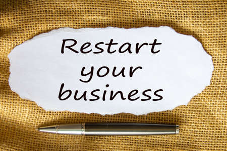 The text 'restart your business' on white paper. Metalic pen. Beautiful canvas background. Business concept.