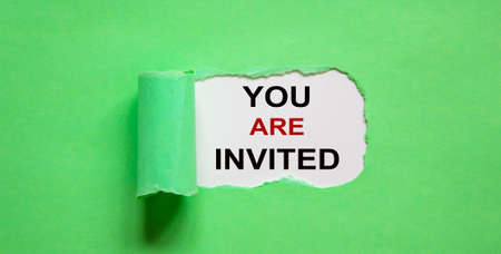 The text 'you are invited' appearing behind torn green paper.