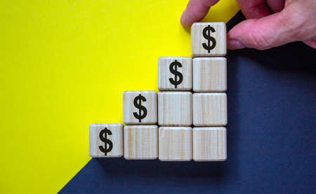 Business concept growth success process. Close up man hand arranging wood block with dollar sign stacking as step stair on paper yellow and black background, copy space. Zdjęcie Seryjne