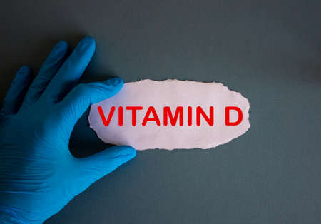 Hand in blue glove with white small paper. Concept word vitamin d.