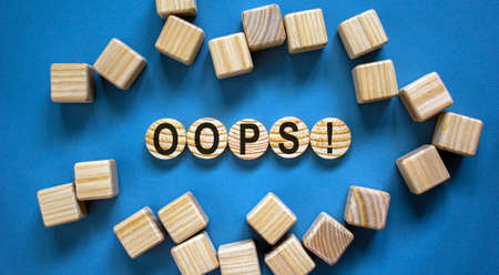 Oops sign on wooden cut circles. Wooden cubes. Beautiful blue background, copy space. Concept.