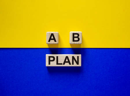 Wooden block with word 'plan'. Wooden cubes with letters A and B. Beautiful yellow and blue background. Copy space. Concept of choice. Stock Photo