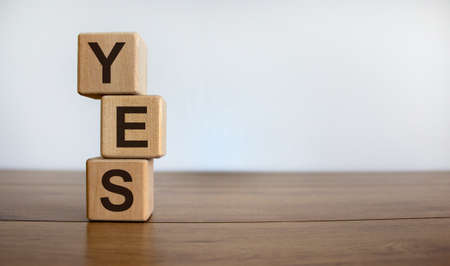Wood cubes with word 'yes' on wooden table, beautiful white background, copy space. Business concept.