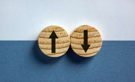 Conceptual image of choice and direction. Wooden circles with arrows pointing in opposite directions. Beautiful white and blue background, copy space. 스톡 콘텐츠