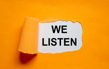 The text 'we listen' appearing behind torn orange paper. Business concept. Copy space. 스톡 콘텐츠