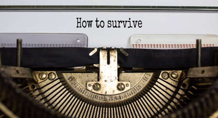 Text 'how to survive' typed on retro typewriter. Business concept. Beautiful background. Archivio Fotografico