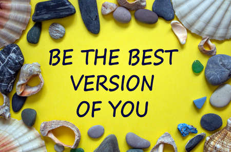 Text 'be the best version of you' on a beautiful yellow background. Sea stones and seashells. Concept. Zdjęcie Seryjne