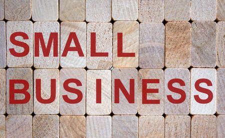 Wooden blocks form the words 'small business'. Beautiful wooden background.