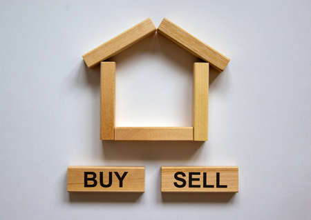 Wooden blocks form the words 'buy sell' near miniature house. Beautiful white background, copy space. Business concept.