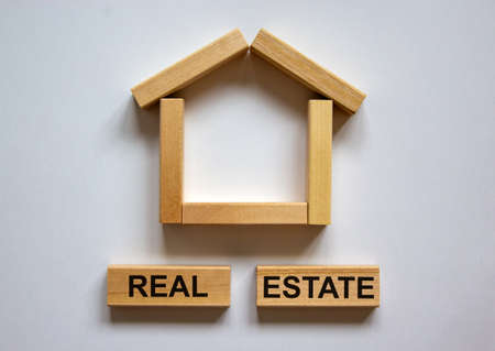 Wooden blocks form the words 'real estate' near miniature house. Beautiful white background, copy space. Business concept.