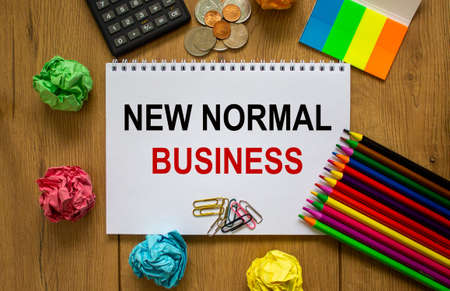 White note with inscription 'new normal business' on beautiful wooden table, colored paper, colored pencils, paper clips, coins and calculator. Business concept.
