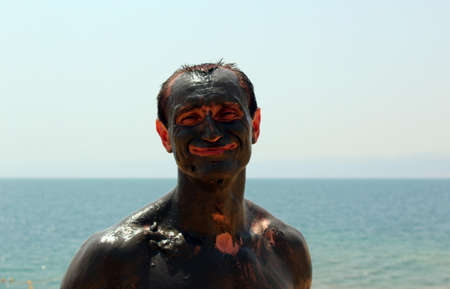Smiling man smeared with mud, visible minor patches of skin. Dead Sea. Jordan.