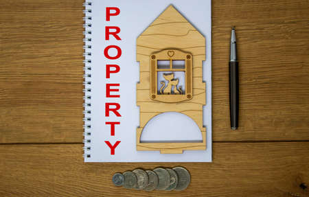 White note with inscription 'property' on beautiful wooden table, metalic pen, coins and miniature wooden house. Business concept.