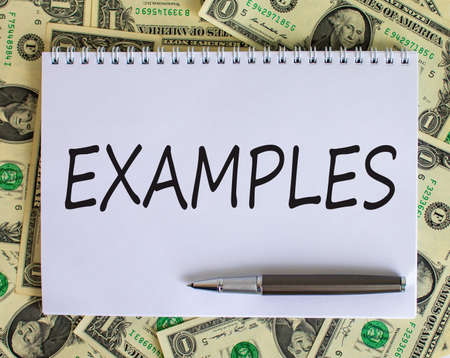 White note with inscription 'examples' on beautiful background from dollar bills and metalic pen. Business concept.
