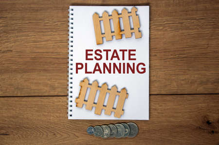 White note with inscription 'estate planning' on beautiful wooden table, metalic coins and miniature wooden fence. Business concept.