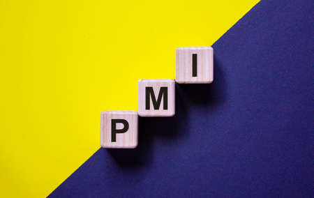 Wood cubes with word 'PMI' stacking as step stair on paper blue and yellow background, copy space. Business concept.