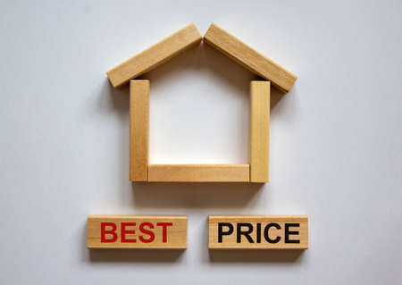 Wooden blocks form the words 'best price' near miniature house from wooden blocks. Beautiful white background, copy space. Business concept.